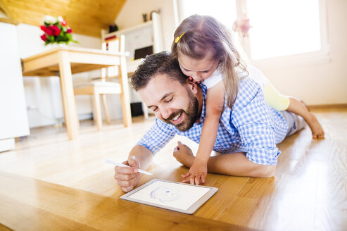 Father and daughter lying on floor, drawing on digital tablet - HAPF000537