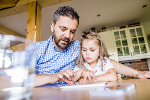 Father and daughter sitting at home using digital tablet - HAPF000540