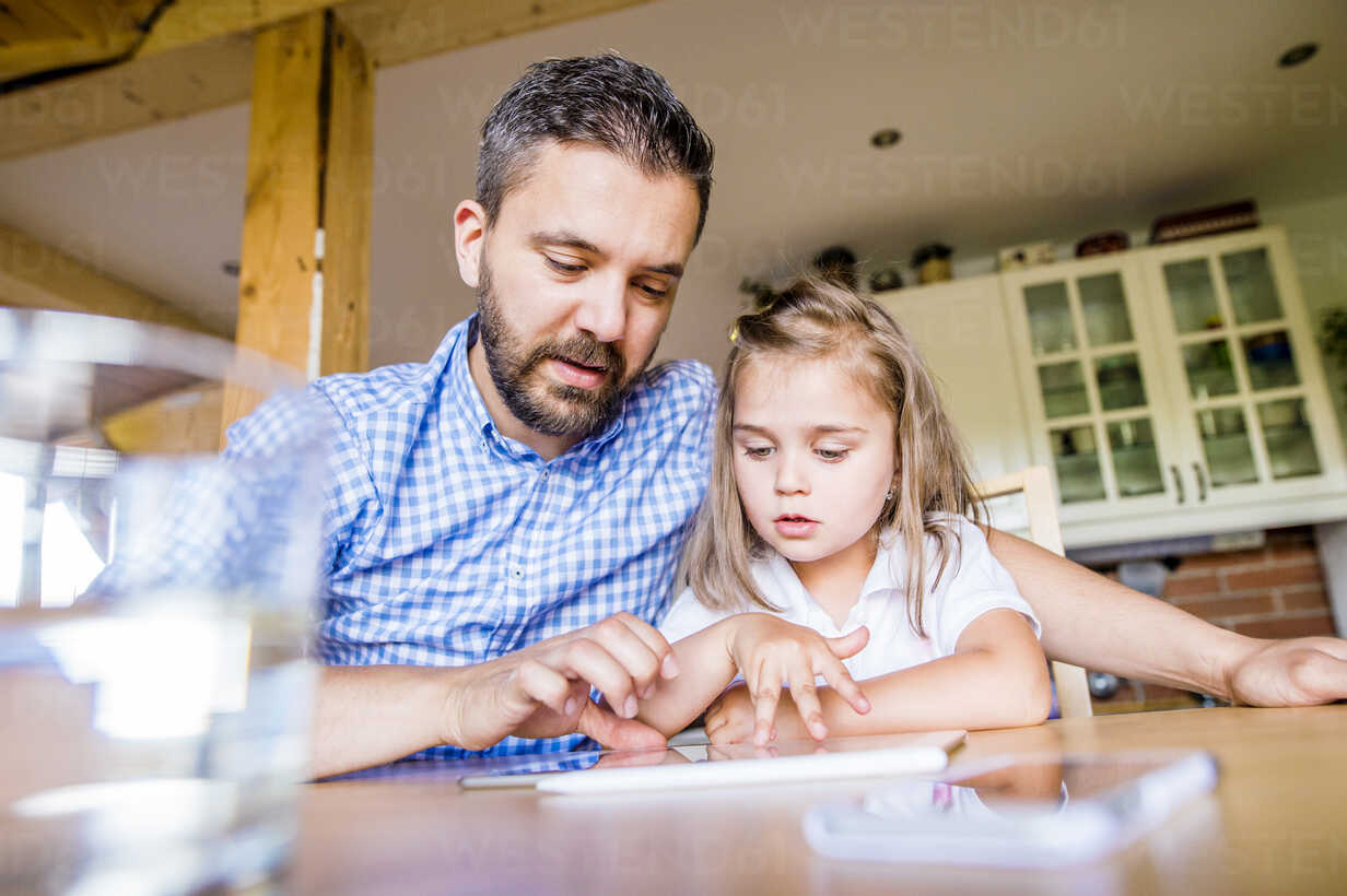 Father and daughter sitting at home using digital tablet - HAPF000540 - HalfPoint/Westend61