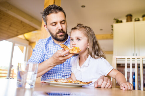 Father feeding his little daughter with pizza - HAPF000543