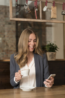 Portrait of smiling young woman in a coffee shop looking at her smartphone - KAF000158