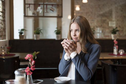 Portrait of young woman drinking coffee in a coffee shop - KAF000164