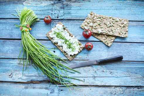 Crispbread, cream cheese, bunch of chive, cocktail tomatos and knife on turquoise wood - MAEF011846