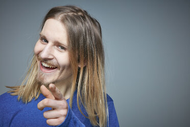 Portrait of laughing young man with long blond hair pointing on viewer - RHF001656