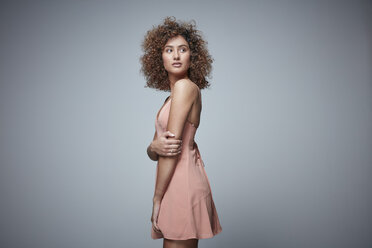 Portrait of redheaded woman with curly hair wearing salmon coloured dress - RHF001671