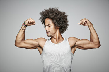 Portrait of man with afro flexing his muscles - RHF001680