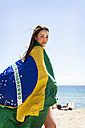 Young brunette woman playing with Brazilian flag at the beach - VABF000643