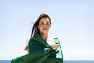 Young brunette woman playing with Brazilian flag at the beach - VABF000646