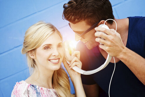 Two friends hearing music together with one headphone - GDF001037