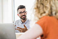 Young professional talking to colleague in office - UUF007853