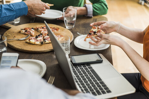 Colleagues at table with cell phone and laptop having a pizza - UUF007898