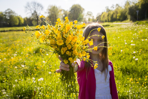 Girl on a meadow gifting bunch of buttercups to viewer - SARF002800