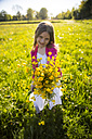 Girl on a meadow gifting bunch of buttercups to viewer - SARF002803