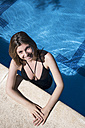 Portrait of smiling woman standing in swimming pool at the edge looking up - ABZF000743