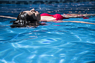 Woman floating on water of a swimming pool - ABZF000746