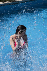 Woman standing in a pool being splashed with water - ABZF000749