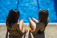 Two talking women sitting on the edge of a pool with glasses of orange juice - ABZF000758