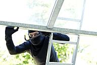 Burglar on ladder peeking at open roof window - MAEF011865