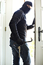 Burglar with pearl necklace in pocket leaving house - MAEF011868