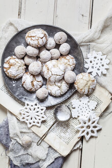 Home-baked Christmas cookies with powdered sugar on old book - SBDF002968