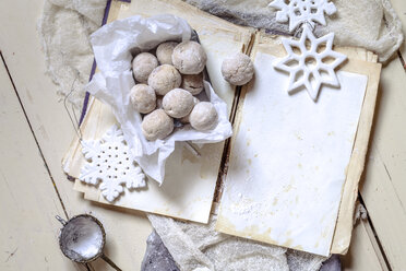 Home-baked Christmas cookies  with powdered sugar on old book - SBDF002971