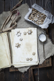 Home-baked Christmas cookies with powdered sugar on old book - SBDF002974