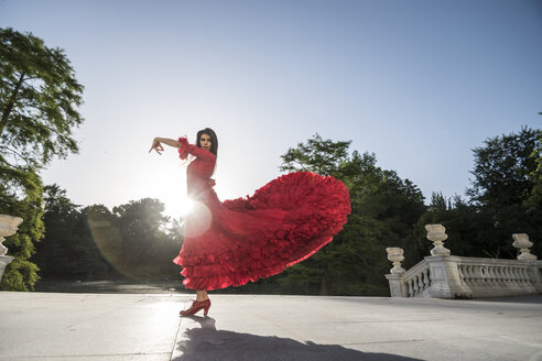 Woman dressed in red dancing flamenco on terrace at backlight - ABZF000766