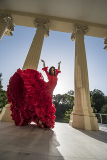 Woman dressed in red dancing flamenco on terrace at backlight - ABZF000769