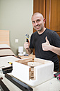 Man assembling furniture at home, thumbs up - RAEF001241