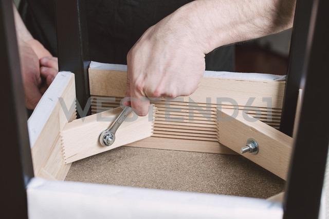 Man assembling furniture at home - RAEF001244