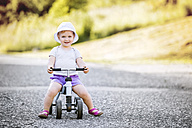 Portrait of smiling toddler girl on toy car - HAPF000545