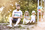 Father and his little daughters sitting side by side on the ground in a park - HAPF000548