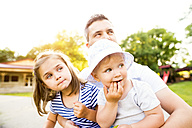 Father and his little daughters watching something in a park - HAPF000551