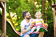 Father looking at his little daughter sitting on a swing of playground - HAPF000560