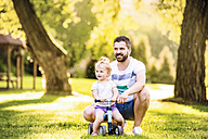 Father and his little daughter with toy car in a park - HAPF000563