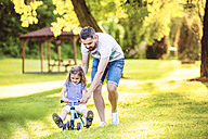 Father and his little daughter with toy car in a park - HAPF000566
