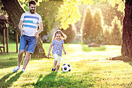 Happy little girl playing soccer with her father in a park - HAPF000572