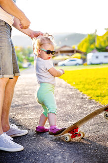 Portrait of toddler girl wearing sunglasses kicking skateboard - HAPF000584