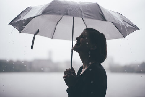 Laughing woman with umbrella on a rainy day - DASF000050