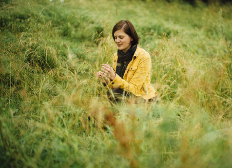 Woman crouching on a meadow - DASF000056