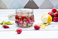 Glass of pickled red radishes and ingredients on wood - LVF005049