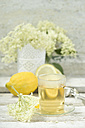 Elder flower tea, tea cup and elderflowers, lemon in the background - ASF005923