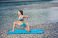 Woman practicing yoga by the riverside - YNF000002