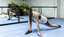 Young woman doing stretching exercises in gym - MGOF002035