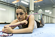 Young woman doing stretching exercises in gym - MGOF002038