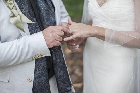 Hands of bride and groom with wedding ring - ZEF008862
