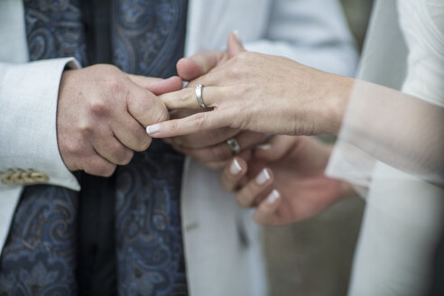 Hands of bride and groom with wedding ring - ZEF008865