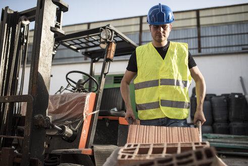 Construction worker pushing wheel barrow with bricks - JASF000866