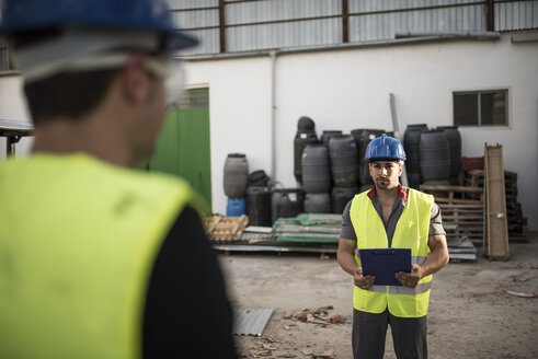 Construction workers talking and looking notebook instructions - JASF000869