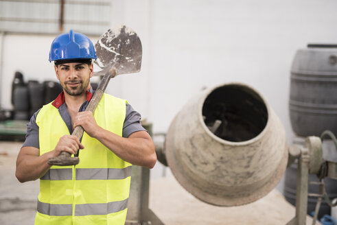 Construction worker next to the concrete mixer - JASF000872